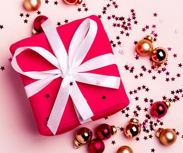 Cadeau rouge sur fond rose avec des boules de Noël rouges et dorées et des étoiles scintillantes